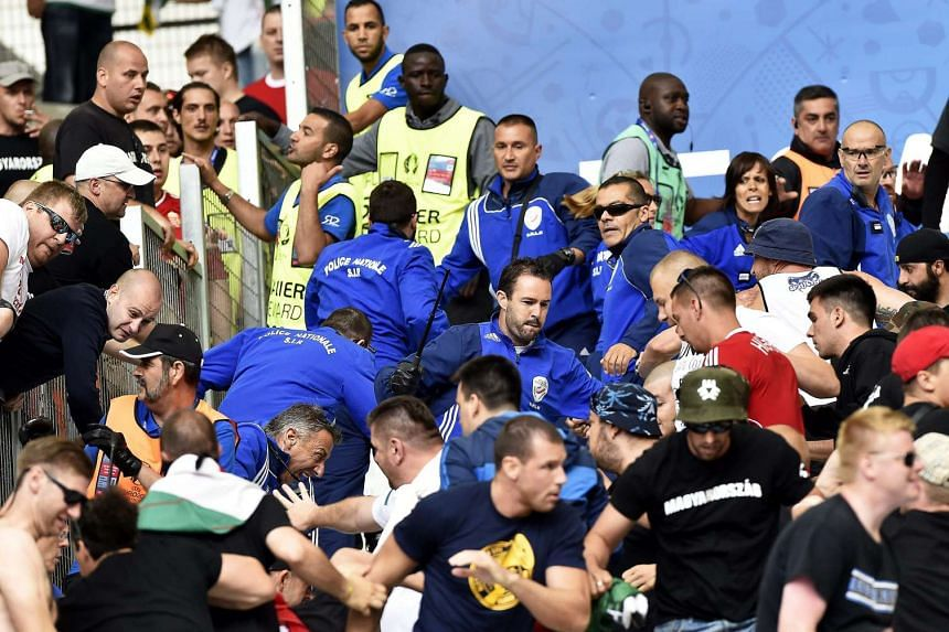 Hungarian supporters clash with police (blue) in the stands.