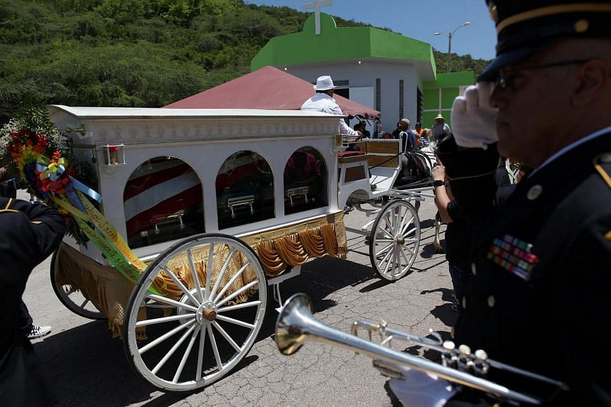 A horse-drawn carriage carries the coffin of Angel Candelario, one of the victims of the shooting at the Pulse nightclub in Orlando, during his funeral procession in his hometown of Guanica, Puerto Rico on June 18.