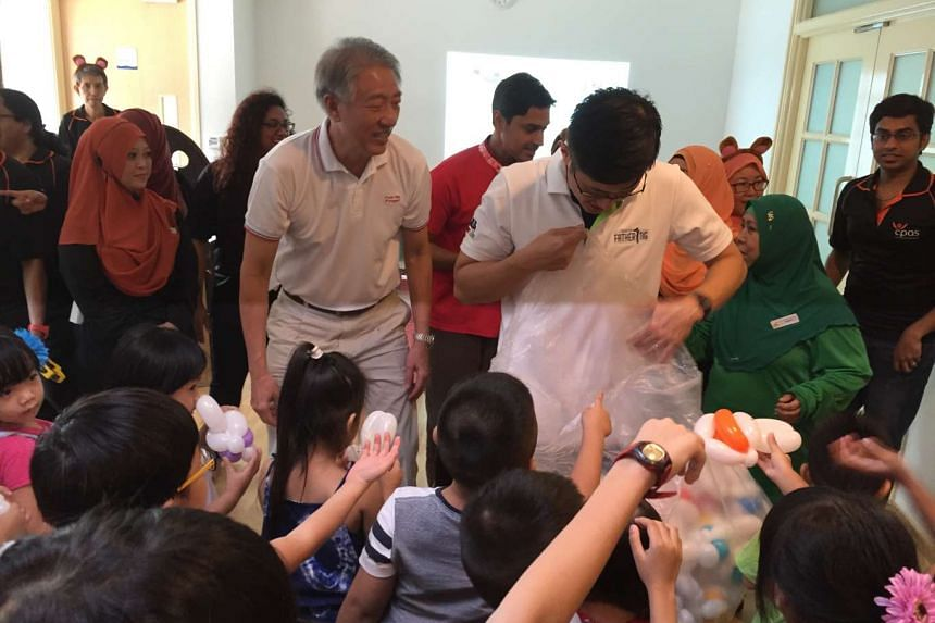 Deputy Prime Minister Teo Chee Hean and North East District Mayor Teo Ser Luck giving children balloons at the launch event.
