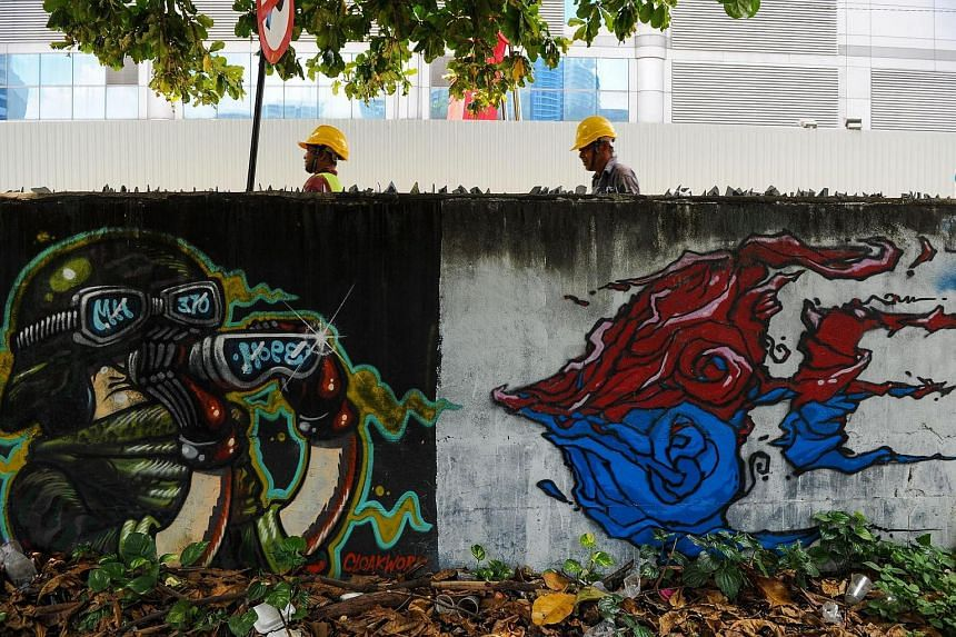 Construction workers walk behind a mural dedicated to missing MH370 on a wall next to a parking lot in Kuala Lumpur on March 24.