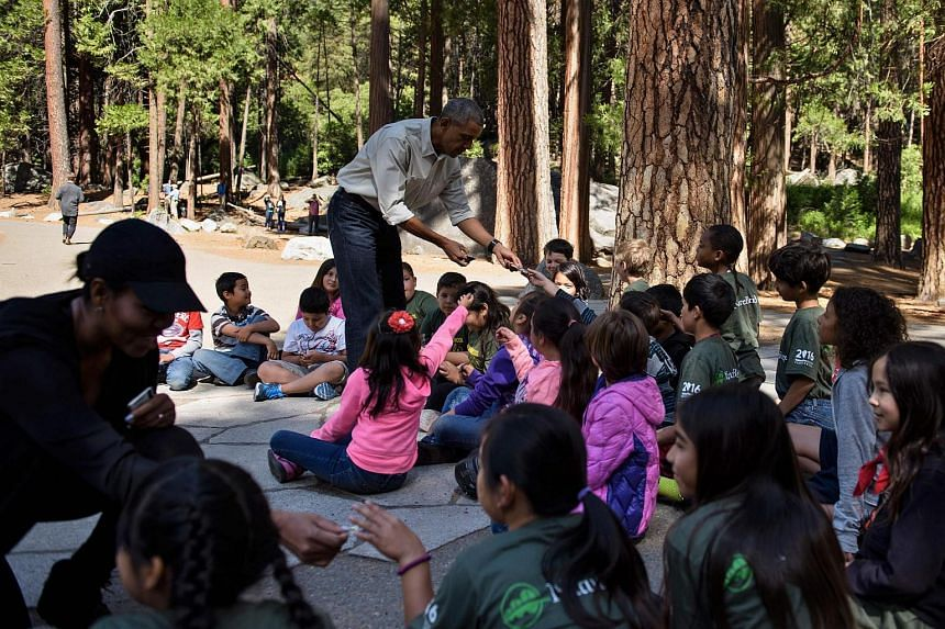 """US First Lady Michelle Obama (left) and US President Barack Obama hand out National Park passes to children for the """"Every Kid in the Park"""" initiative in Yosemite National Park, California."""