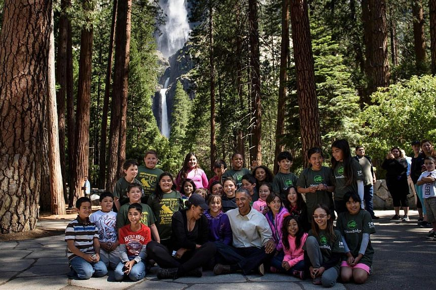 """US First Lady Michelle Obama and US President Barack Obama sit with children after speaking to them about the """"Every Kid in the Park""""  on June 18 in Yosemite National Park, California."""