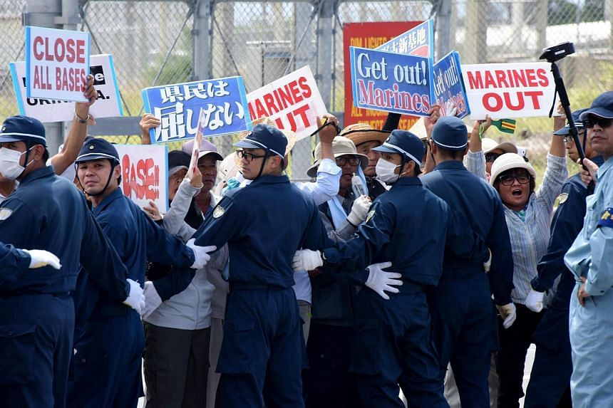 Policemen try to remove people protesting against the presence of US bases, in front of the gate of the US Marine Corps' Camp Schwab in Nago, on the southern island of Okinawa prefecture on June 17.