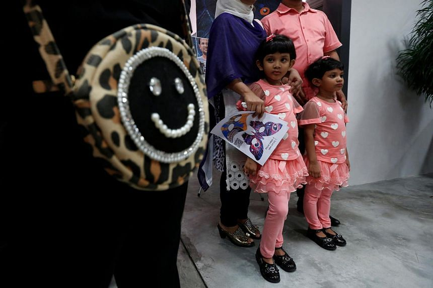 Sanzida (left), 6, looks on beside her younger sister Shahzia, 5, as they and their parents attend an awareness arts show on refugees in Hong Kong on June 16, 2016, after the family fled Bangladesh.
