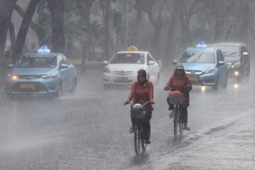 Two people ride bicycles through the rain in Central Jakarta, on June 9, 2016.