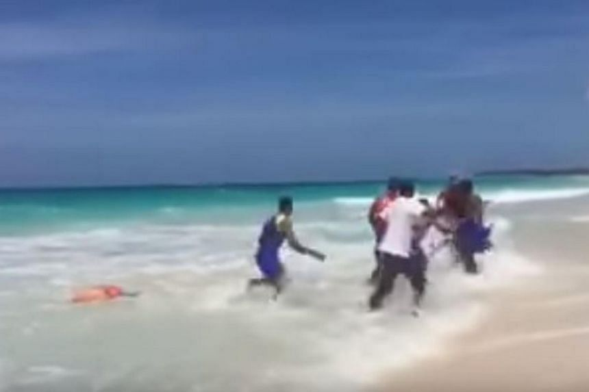The lifeguards dragging the shark from the water.