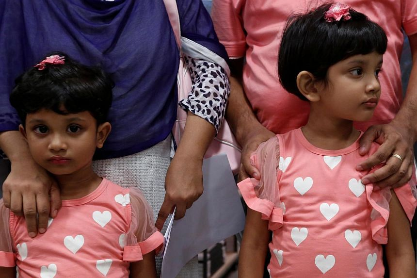 Shahzia (left) and her sister Sanzida pose with their parents in Hong Kong on June 16 after the family fled Bangladesh.