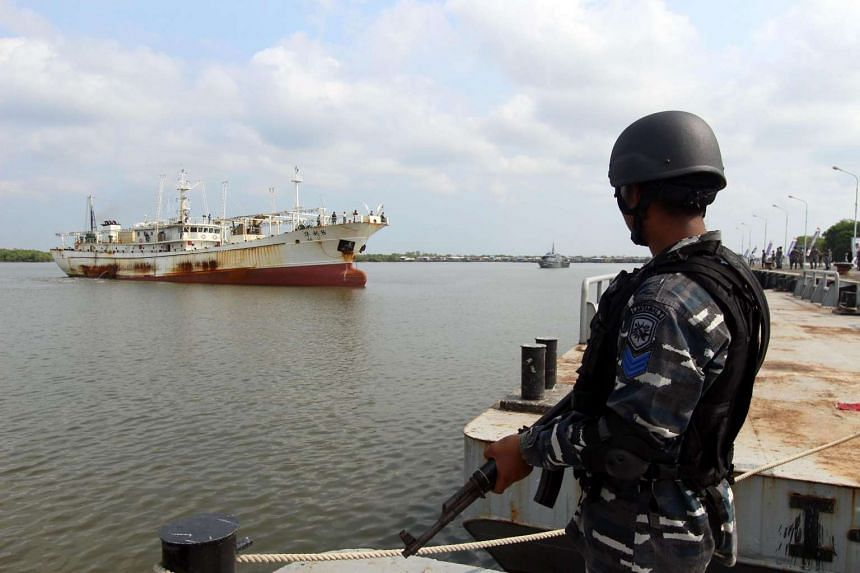 A member of the Indonesian navy standing before the Chinese trawler Hua Li-8 in Belawan, North Sumatra, on April 23, 2016.