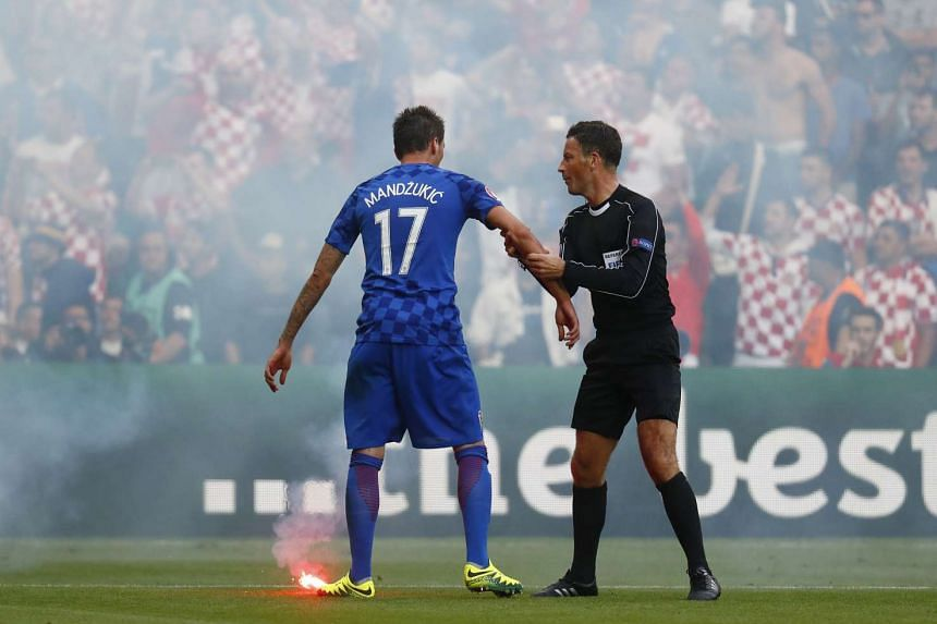 A flare is thrown onto the pitch by fans as Croatia's Mario Mandzukic speaks with referee Mark Clattenburg.