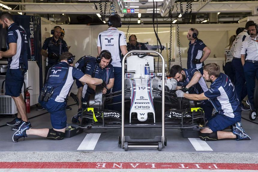 Mechanics work on the car of Brazilian Formula One driver Felipe Massa of Williams during the third practice session at the Baku city circuit, in Baku, Azerbaijan on June 18, 2016.