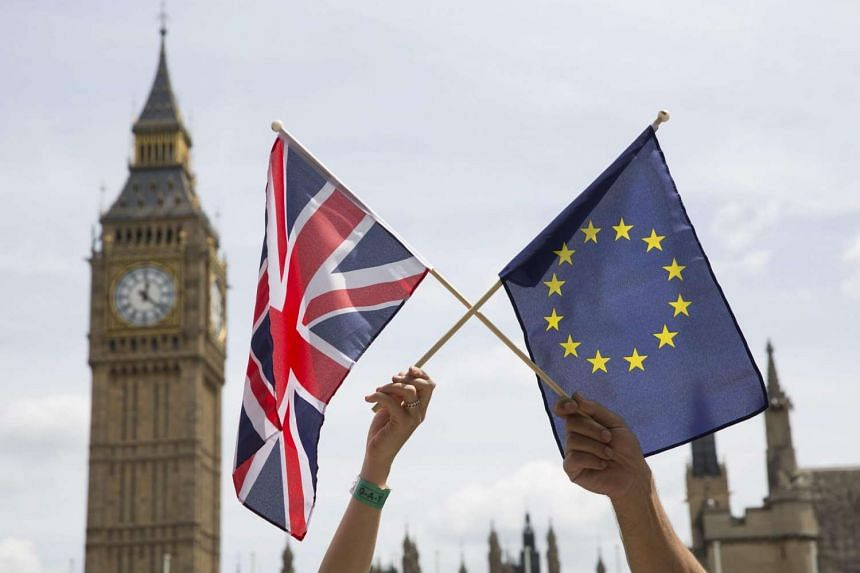 Members of the public hold flags at a stay in, pro EU Referendum event in Parliament Square, Central London, on June 19, 2016.