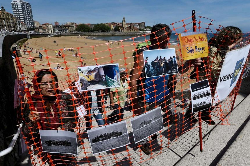 A group of activists put up a wall of plastic on the beach of San Lorenzo de Gijon to request the opening of borders to refugees, in Gijon, northern Spain, on June 19, 2016.