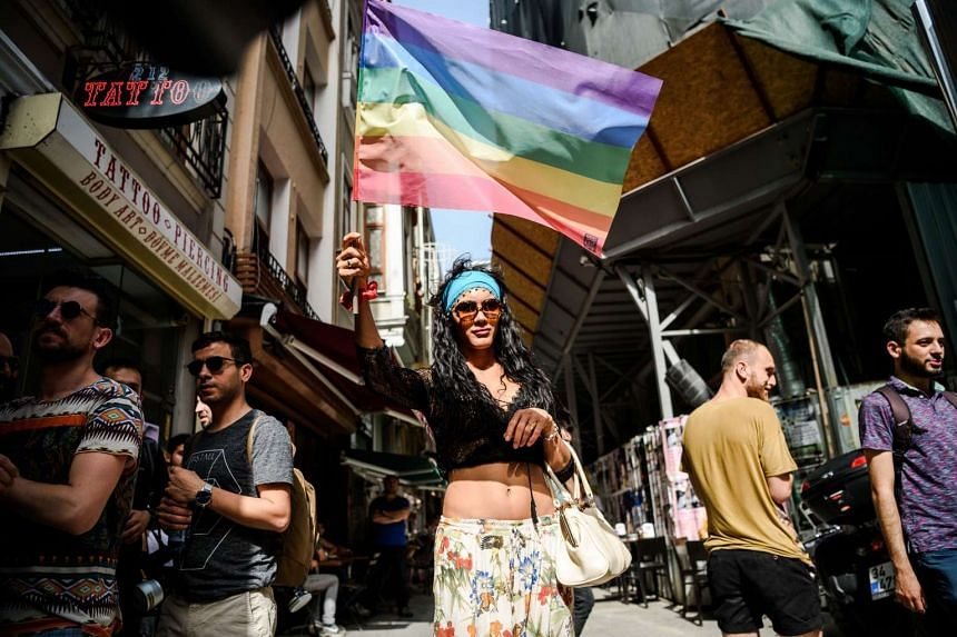 People cover their face with t-shirts as Turkish anti-riot police officers fire rubber bullets to disperse demonstrators gathered for a rally staged by the LGBT community on Istiklal avenue in Istanbul on June 19, 2016.