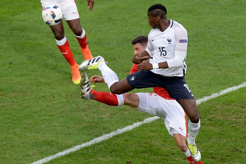 France's midfielder Paul Pogba (right) vies with Switzerland's defender Fabian Schaer during the Euro 2016 group A football match between Switzerland and France at the Pierre-Mauroy stadium in Lille on June 19, 2016.