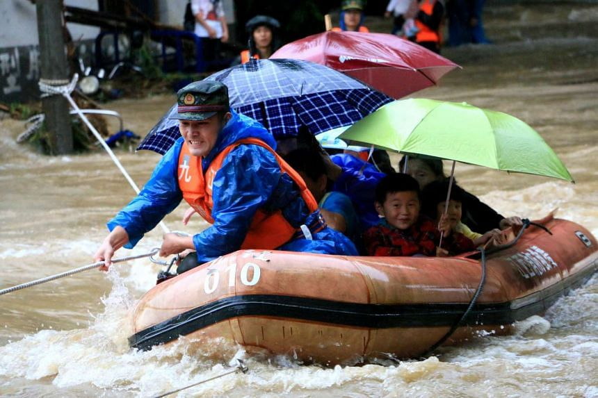 A rescuer grabs a rope to prevent a raft carrying residents from being flushed away as they evacuate from a flooded area in Jiujiang, Jiangxi province, on June 19, 2016.