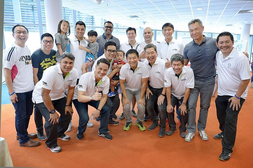 Social and Family Development Minister Mr Tan (wearing yellow sneakers) at the launch of the Dad's for Life football team at yesterday's Dad's Day Out carnival.