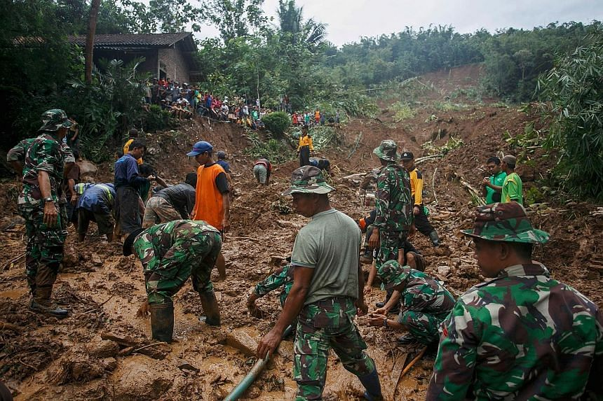 Indonesian soldiers (above) searching for landslide victims at Caok village in Purworejo, Central Java province, yesterday. Thousands of homes in Central Java have been swamped in water, with the affected areas including Kampung Sewu (below) in the c