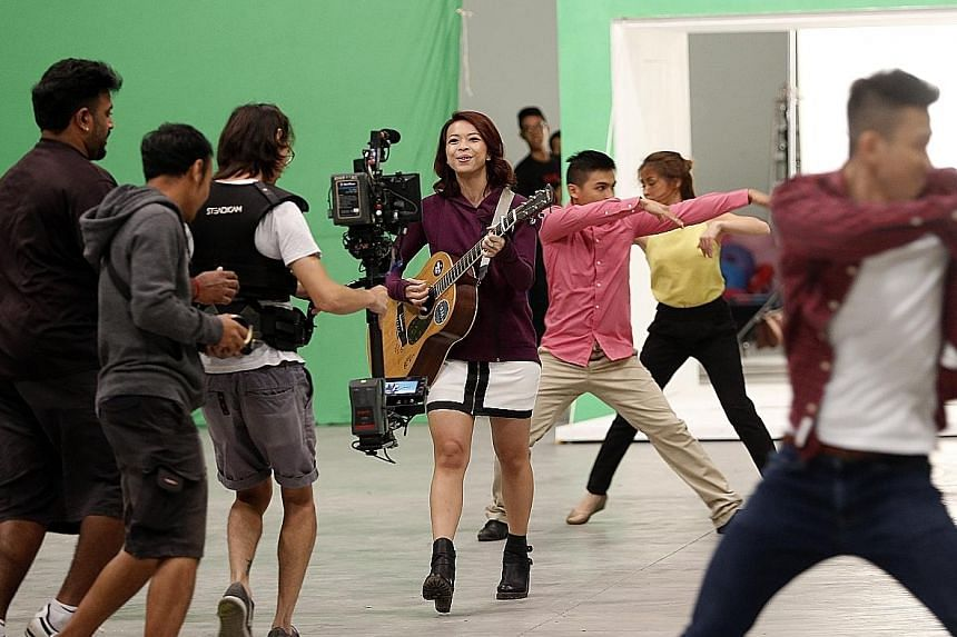"""Vocalist Sara Wee from local band 53A, which performs this year's NDP theme song. Shooting the music video for the song involved using """"green screen"""" backdrops, which can be digitally replaced with other images."""