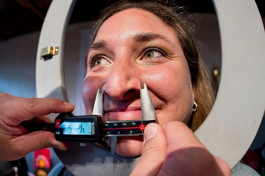 Ms Susanne Kloiber's nose being measured by a judge at the World Championship of Noses in the southern German city of Langenbruck, Bavaria. At 6.95cm in length and 4.26cm in width, her appendage pipped rival big noses, making her the winner of the co