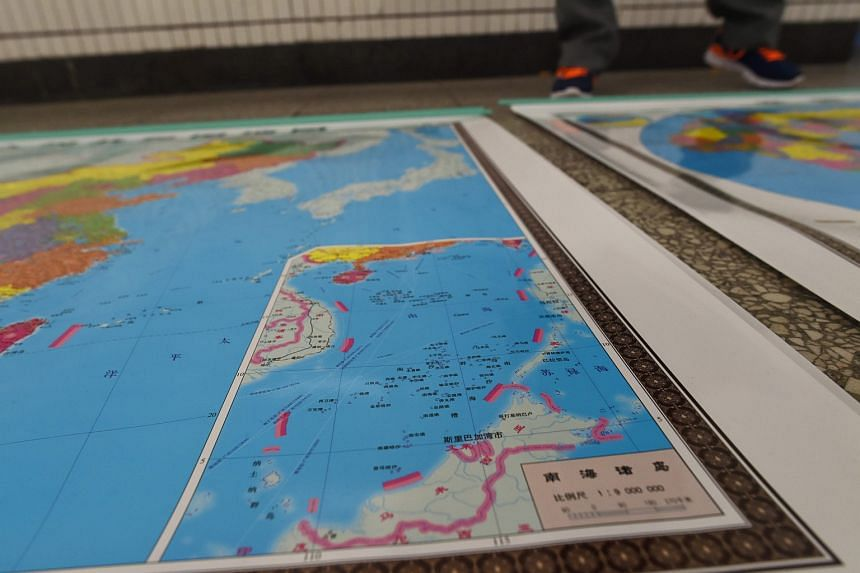 A vendor stands behind a map of China including an insert with red dotted lines showing China's claimed territory in the South China Sea, in Beijing.