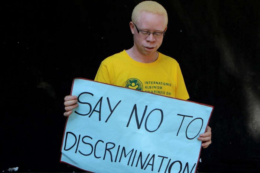 A person holds a placard during an Albinism awareness campaign in Harare, Zimbabwe.