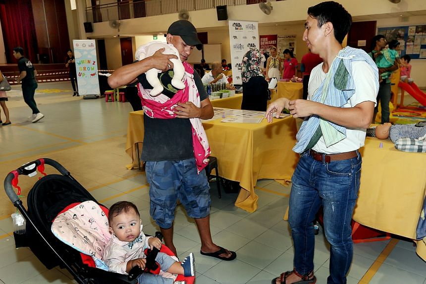 Fathers participating in an event to learn how to use baby wearing techniques.