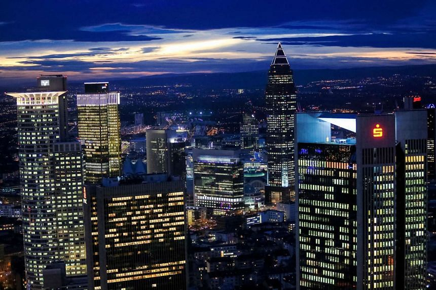 Skyscrapers stand illuminated on the city skyline at dusk in Frankfurt, Germany.