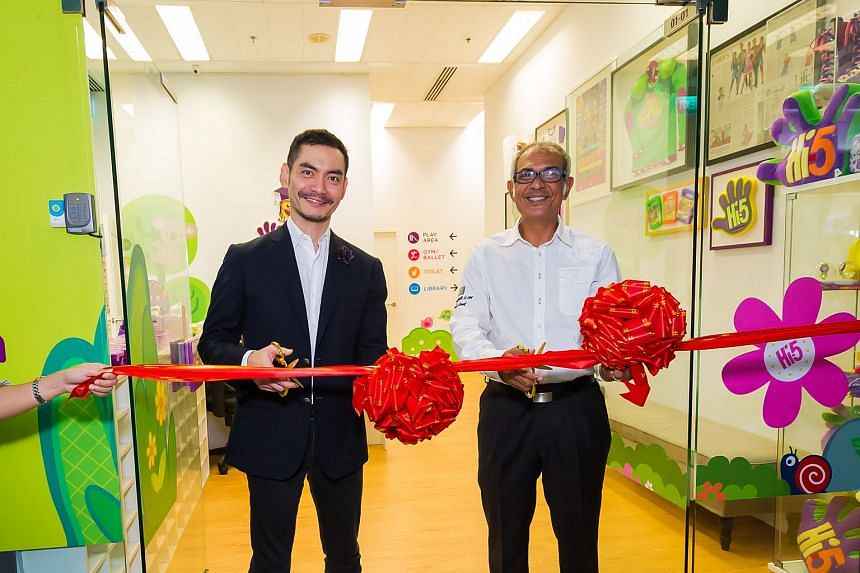 Chairman of Hi-5 World Datuk Jared Lim and Christopher cutting the ribbon to mark the opening of the House of Learning in Singapore.