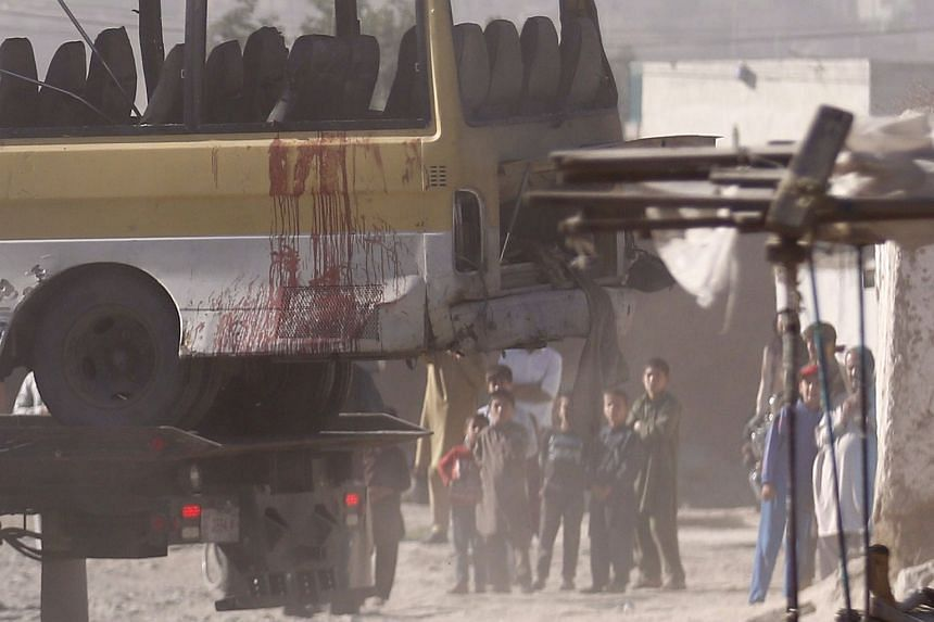Afghan authorities move the damaged mini-bus that was attaked by a suicide bomber in Kabul, Afghanistan,  on June 20.