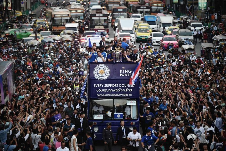 Leicester City football players and staff stand with the Premier League trophy whilst surrounded by fans during the open-bus parade in Bangkok on May 19.