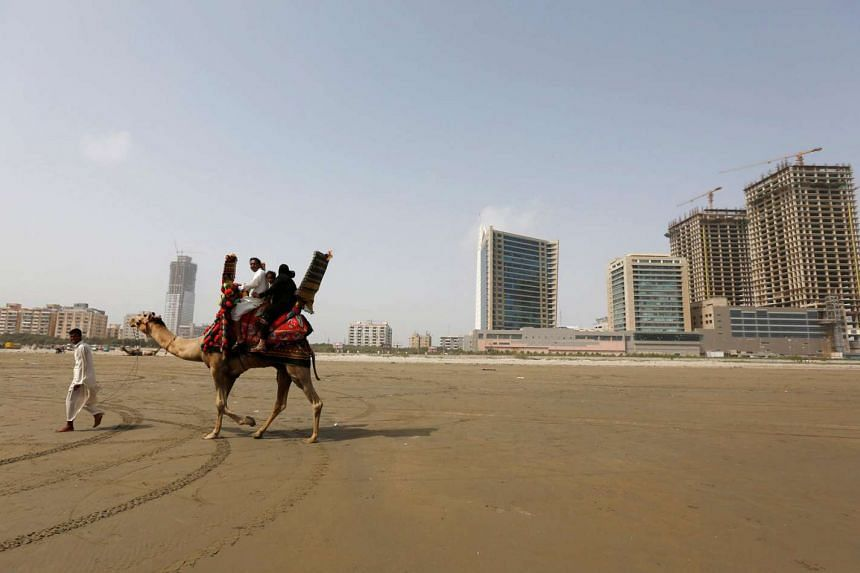 A family rides a camel past the construction of an office building and mall complex on Clifton beach in Karachi, Pakistan.