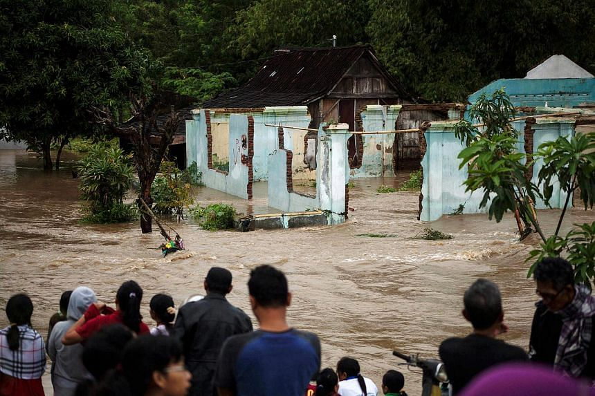 People stand in front of a flooded area in Kampung Sewuresidential area in Solo, Central Java province, Indonesia, on June 19, 2016.