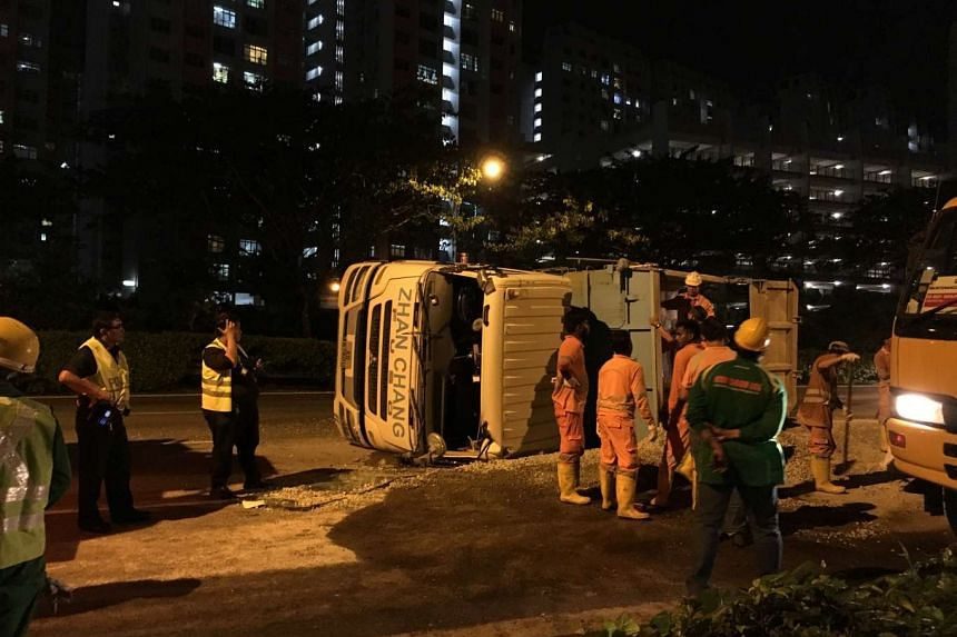 Workers clearing gravel along the Tampines Expressway after a truck overturned  during the evening rush hour on June 20, 2016.