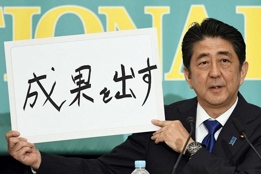 """Japanese Prime Minister Shinzo Abe shows a placard reading """"Produce Results"""" at a party leaders' debate in Tokyo, on June 21, 2016."""