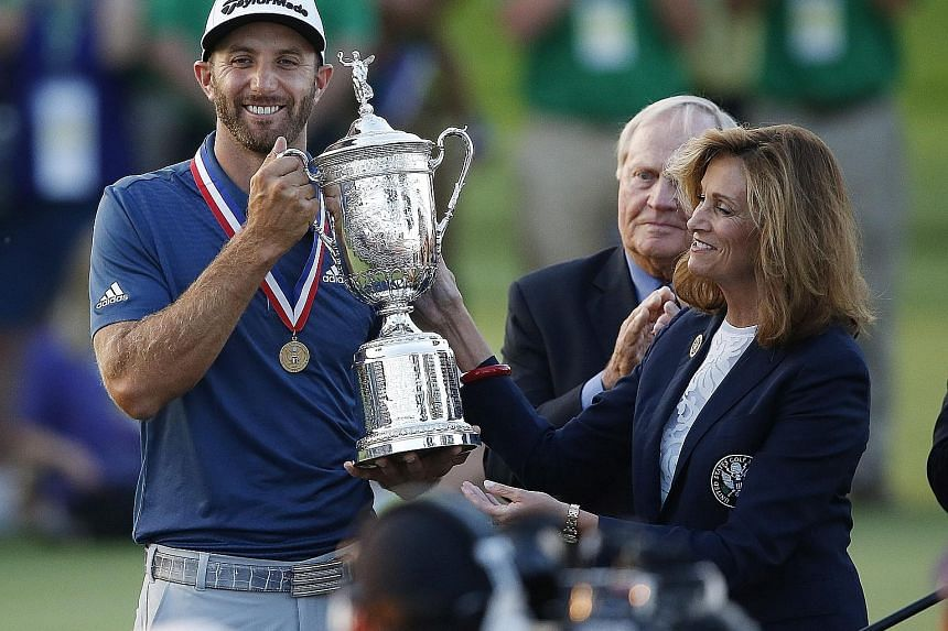 Johnson being presented the trophy after winning the US Open, his first Major, on Sunday.