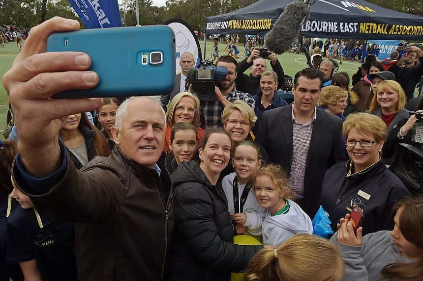 Australian Prime Minister Mr Turnbull taking a wefie with supporters and young netball players during a visit to the H.E. Parker Netball Complex in Melbourne last Saturday. Opposition leader Mr Shorten (centre) with supporters during a visit to the M