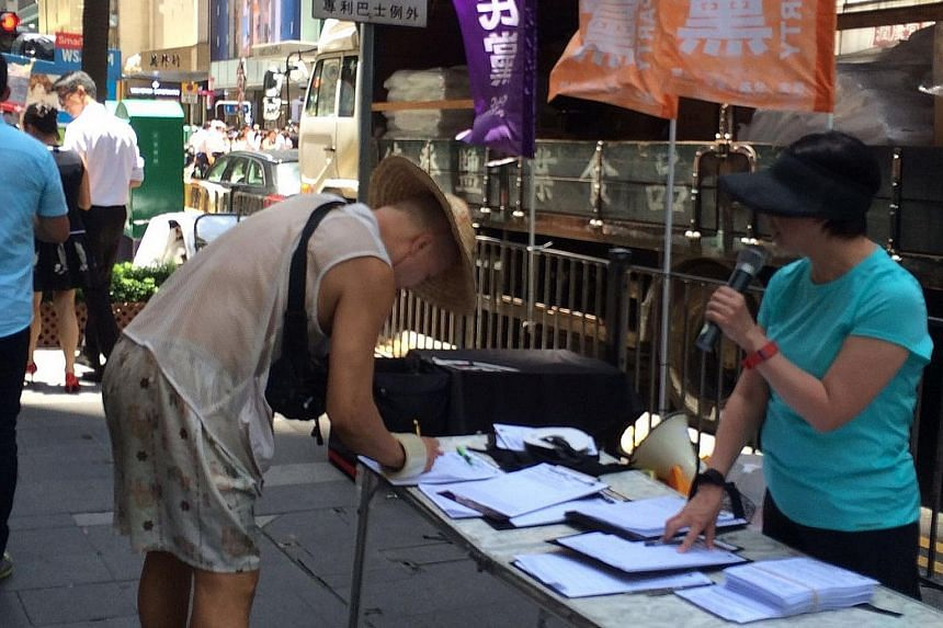 Passers-by in Hong Kong's central district yesterday being invited to sign a street petition calling for the release of the owners of Causeway Bay Books.