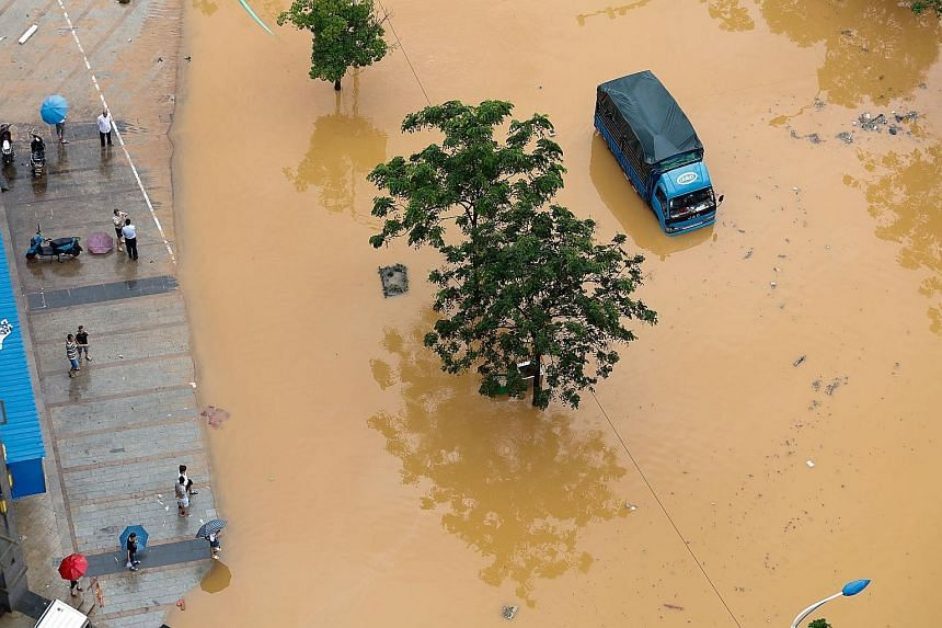 Part of a road is flooded in Jiujiang, Jiangxi Province, on Sunday. Storms pushed water levels in rivers to dangerous levels, leading to crop damage and the collapse of 10,500 houses, Xinhua news agency reported.