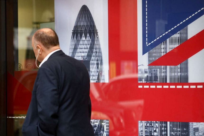 A pedestrian passes a window displaying the British Union flag in London on June 10, 2016.