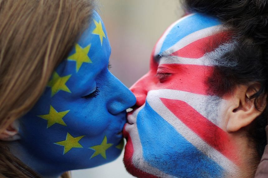 Two activists with the European Union flag and Union Jack painted on their faces kissing in front of Brandenburg Gate in Berlin to protest against the British exit from the EU, on June 19.