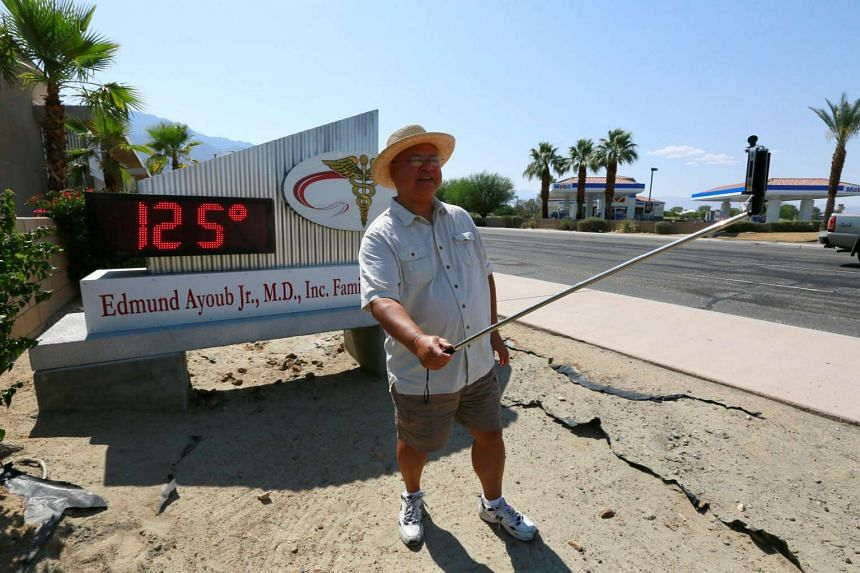 A Palm Springs resident taking a selfie near a thermometer sign which reads 125 deg F (51.7 deg C) on June 20.
