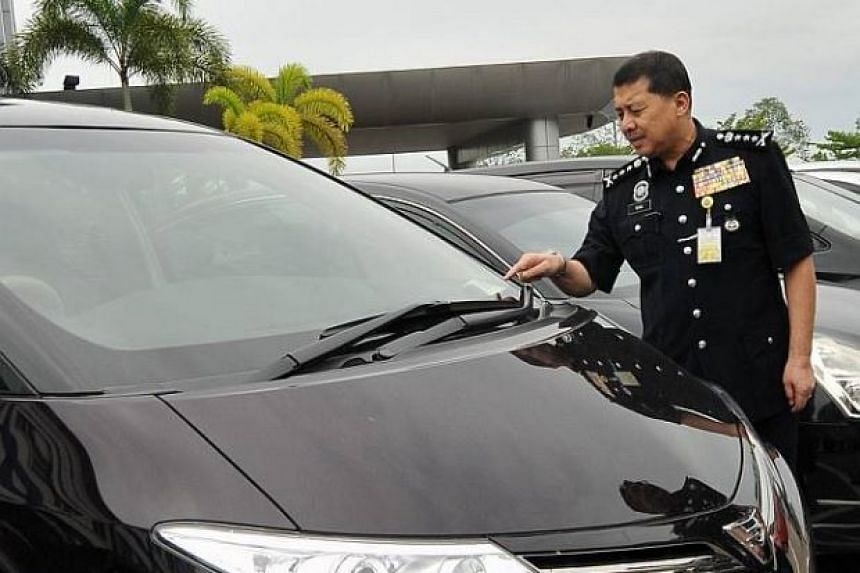 Johor police chief Wan Ahmad Najmuddin Mohd looking at stolen vehicles at the Kulai police headquarters.