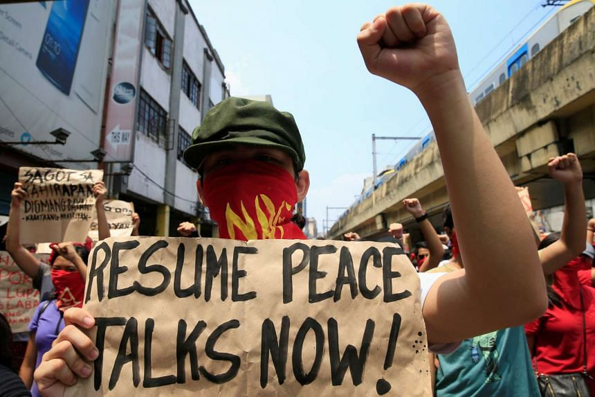 A supporter of the communist National Democratic Front raises his clenched fist as they call for the resumption of peace talks at a protest in Manila, on June 16, 2016.