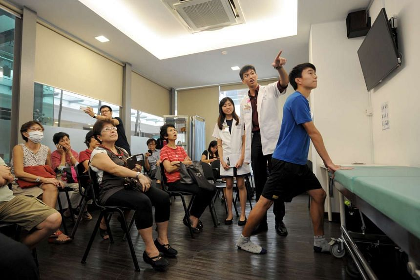 Third-year students from NUS Yong Loo Lin School of Medicine demonstrate exercises to aid with osteoarthritis, on June 21, 2016.