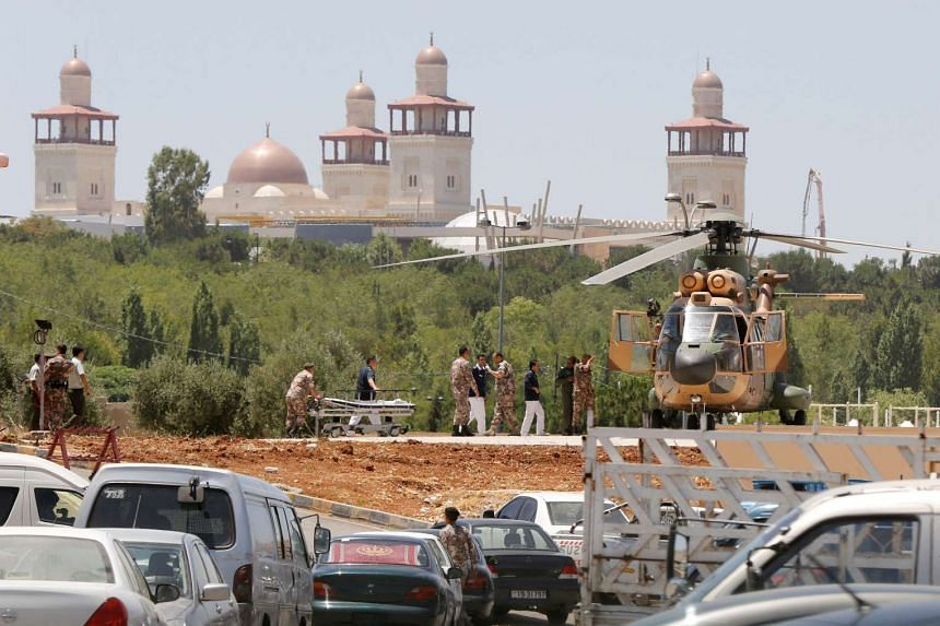 A security member, who was injured during an attack at a camp for Syrian refugees is transported from a military helicopter in Amman, Jordan, on June 21, 2016.