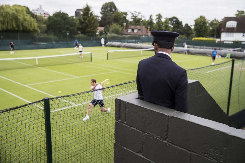 A security staff looks at Richard Gasquet of France at a training session at the All England Lawn Tennis Championships in Wimbledon, on June 21, 2016.