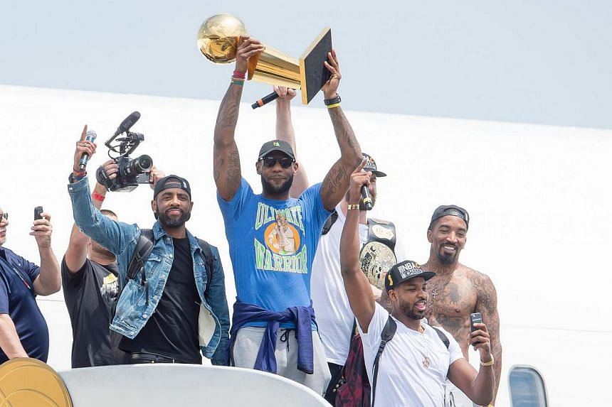 LeBron James (centre) stepping off the Cleveland Cavaliers' team plane carrying the long-coveted National Basketball Association trophy.