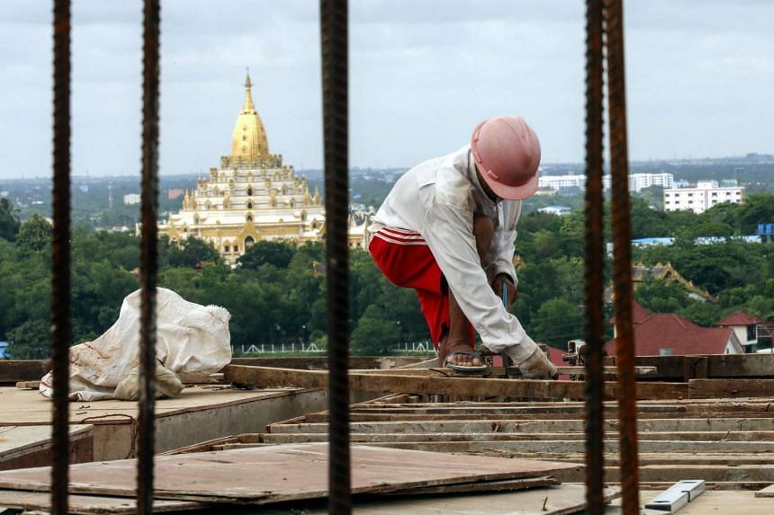 A worker checks a wooden panel on top of a construction site in Yangon, Myanmar, on June 16.