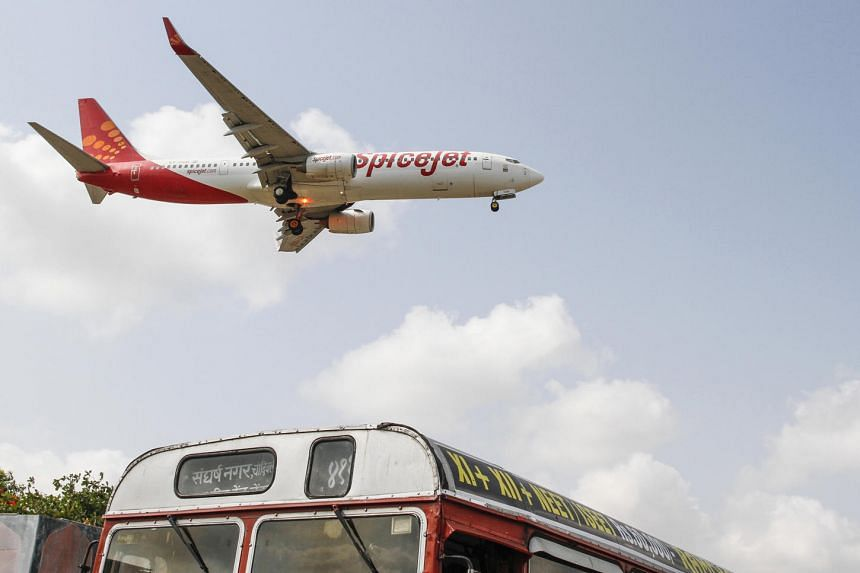A SpiceJet Ltd. aircraft flies over a bus as it prepares to land at Chhatrapati Shivaji International Airport in Mumbai, India, in 2013.