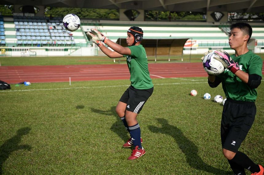 Tanjong Katong Secondary School student and Sabah quake survivor Emyr Uzayr, who wears a scrum cap to protect his head from injury, receiving a ball on the pitch at Bedok Stadium yesterday. The 12-year-old was among 50 children present at the preview